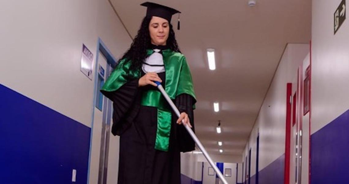 Graduada em Ed. Física, zeladora posa para fotos de formatura com materiais de limpeza